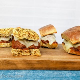 Meatball sandwiches on a cutting board over a blue cloth.