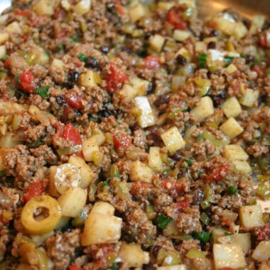 Ground beef with olives, potatoes, and tomato taco filling.
