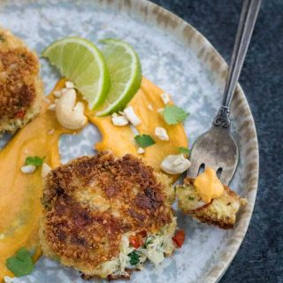 A fork with a bite of crab cake and mango-lime sauce on a great speckled plate.