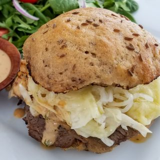 Classic Reuben sandwich made with uncured corn beef, Swiss cheese, sourkraut, and topped with Russian dressing. Served on homemade sprouted rye buns with a salad on the side.