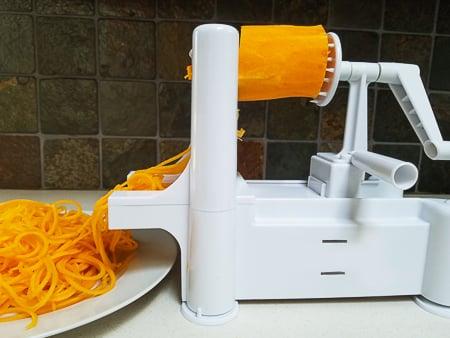 Spiral slicing butternut squash into noodles.