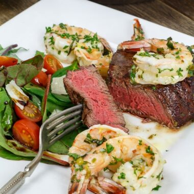 Grilled steak tenderloin topped with shrimp scampi and served with a garden salad. Steak is cut to show a close-up of the rosy pink center, cooked to medium-rare.