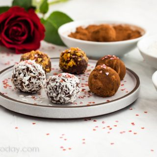 Chocolate truffles on a white place with bowls of coatings beside it.