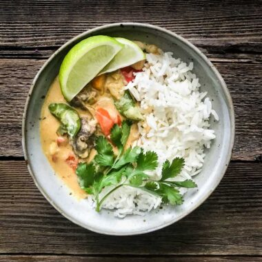 Vegetable coconut curry in a grey bowl with jasmine rice topped with lime and cilantro.