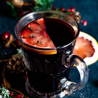 Mulled wine in a clear glass mug with grapefruit