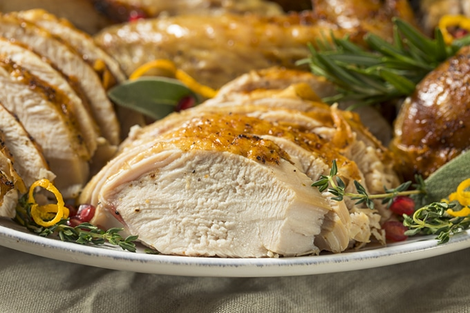 Roasted turkey sliced and served on platter with herbs and lemon peel.
