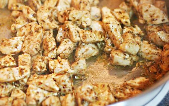 Seasoned chicken in skillet to top Blue Coyote Chicken Nachos