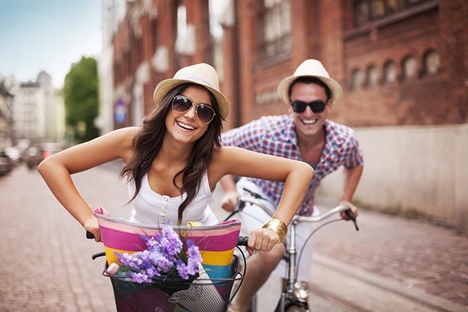 Man and woman riding bikes on a cobblestone street.
